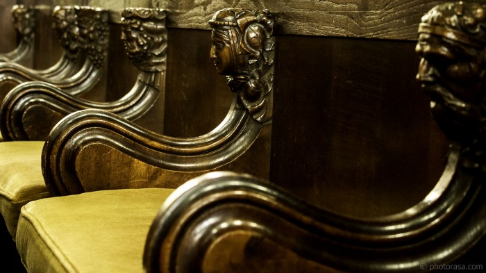 ornately carved heads on choir stalls
