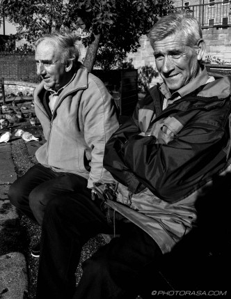 2 old blokes sitting by the pigeons