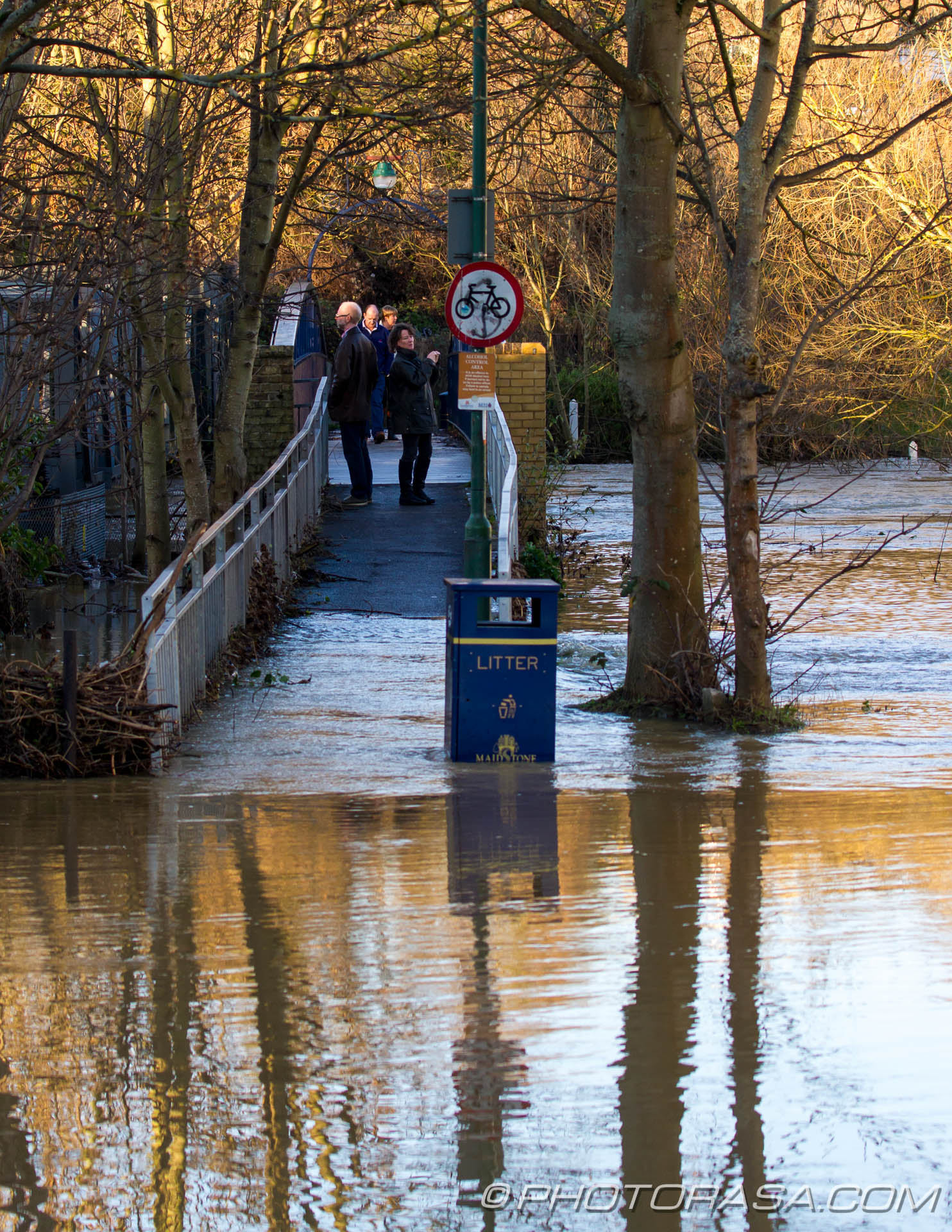 http://photorasa.com/wet-xmas-maidstone-river-medway-floods-town-centre/people-observing-the-flooded-river-on-tovil-footbridge/