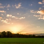 blue sky, sunset and clouds over field