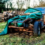 old wrecked sports car in a field with logs on it