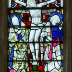 chancel window detail showing jesus on the cross with mary and beloved disciple mournfully looking away