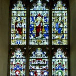 large chancel stained glass window showing jesus on the cross and saints surrounded by angels