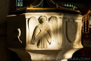 markings on stone font featuring lamb of god angel and shield