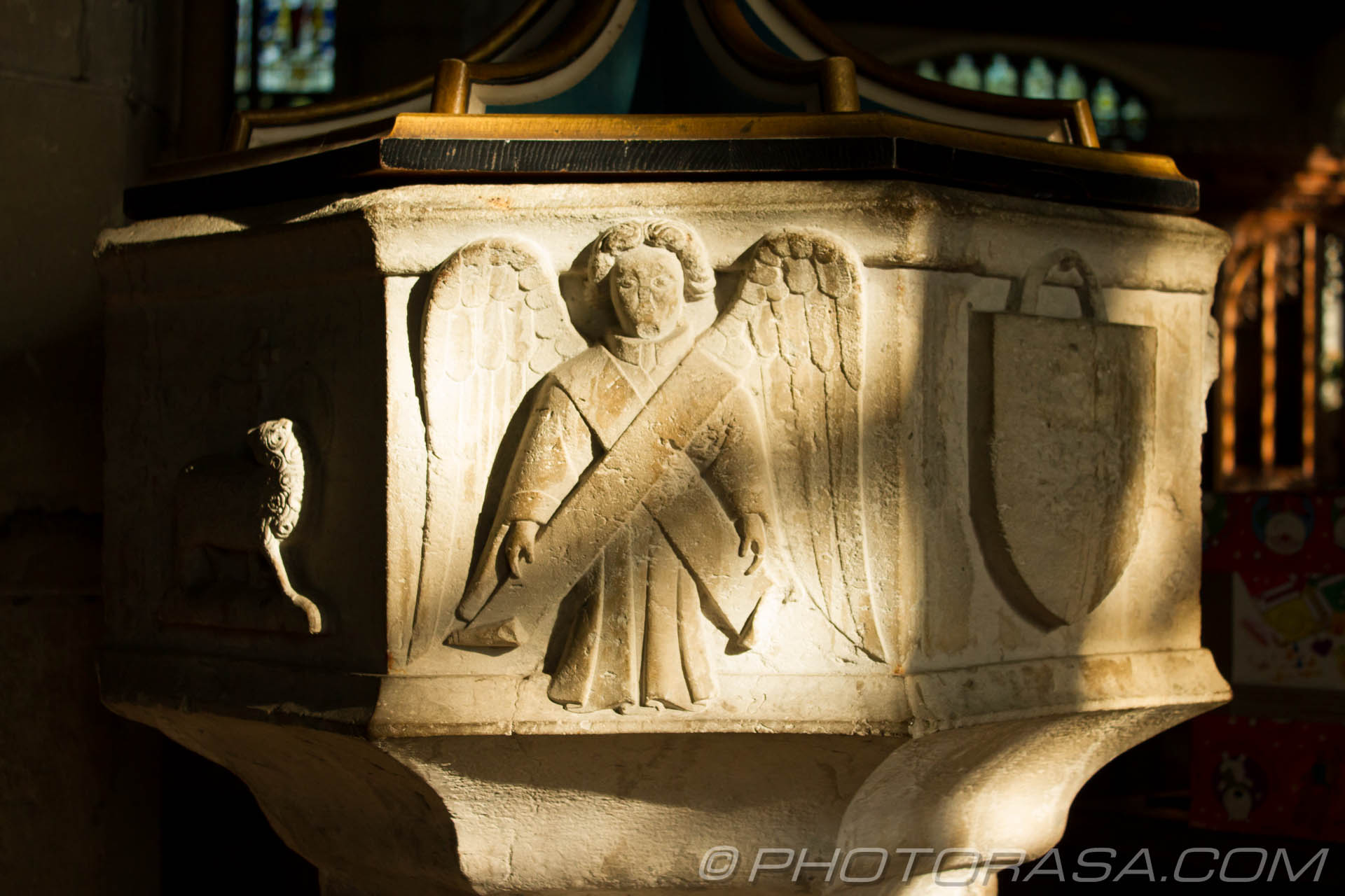 http://photorasa.com/parish-church-st-peter-st-paul-headcorn/markings-on-stone-font-featuring-lamb-of-god-angel-and-shield/