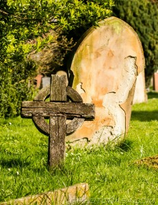 old wooden celtic cross and stone grave