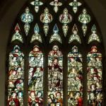 stained glass of jesus surrounded by angels and saints