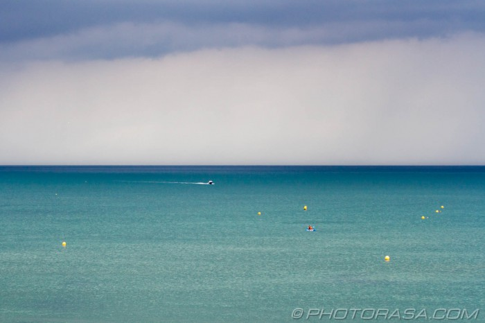 buoys and boats on stormy blue sea