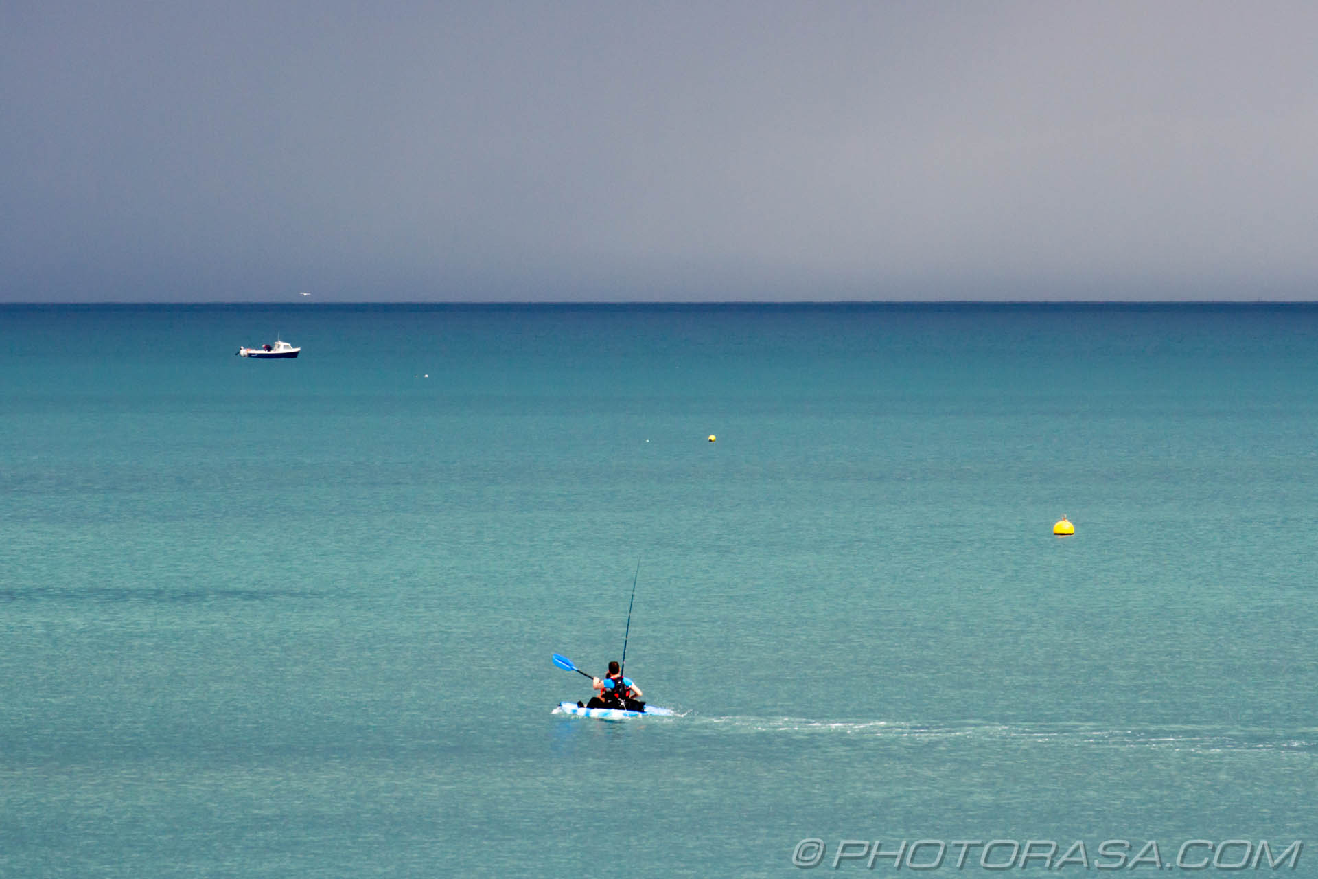 http://photorasa.com/sea-lyme-regis/canoeist-paddling-out-to-dark-blue-sea/