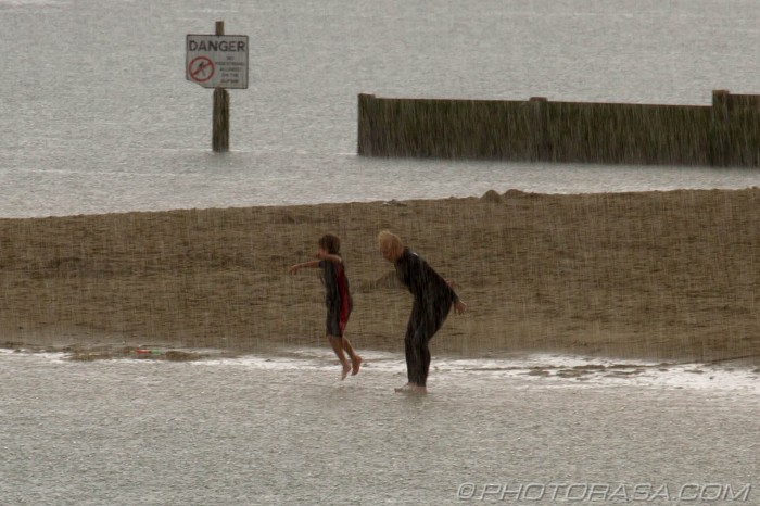 playing on the beach in a rainstorm