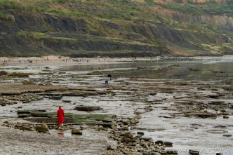 red woman and beachy rocks