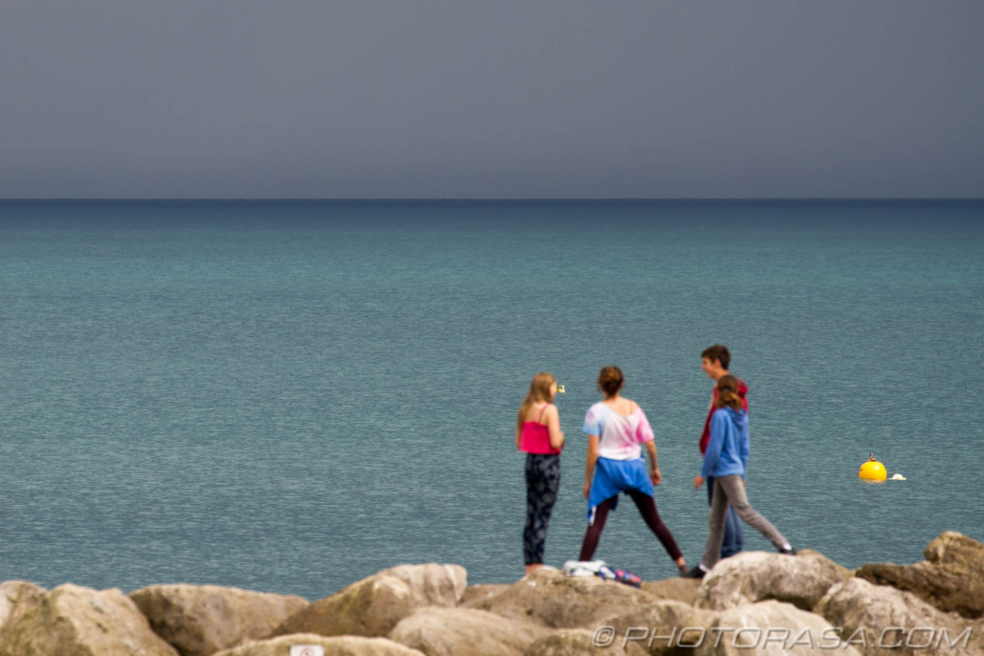 http://photorasa.com/sea-lyme-regis/teenagers-on-the-rocks-by-the-seaside/
