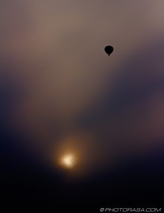 hot air balloon rising above setting sun