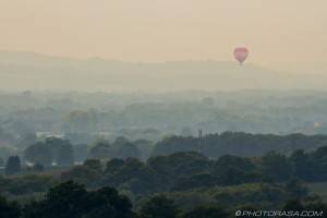 red air balloon over misty woodland