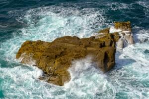 coastal rock engulfed by waves
