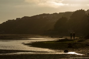couple walking along estuary at sunset and low tide