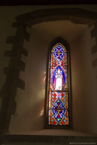 narrow slit stained glass with light shining through