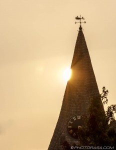 sun peeking from behind loose church spire