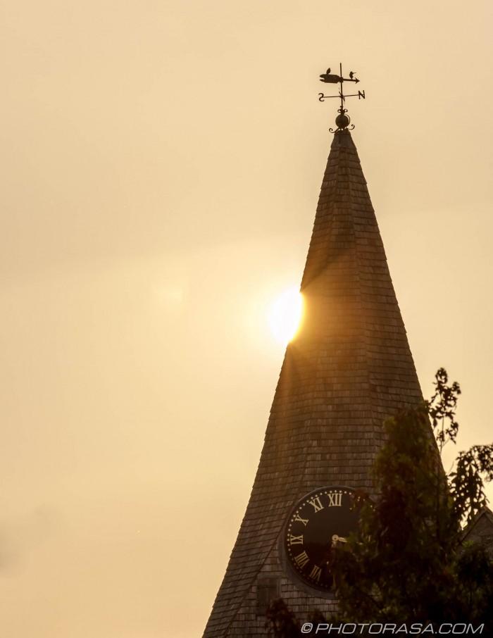 sun peeking from behind loose church spire